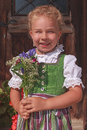 Portrait of a bavarian flower girl little in dirndl with bouquet Stock Image