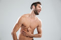 Portrait of a bearded shirtless man doubling up with laughter Royalty Free Stock Photo