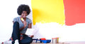Black female painter sitting on floor