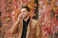 Portrait of beautiful attractive stylish young man speaking on t the phone in autumn park outdoors background Stock Images