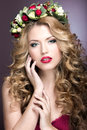 Portrait of a beautiful blond girl with curls and wreath of purple flowers on her head. Beauty face. Royalty Free Stock Photo