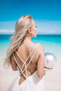 Portrait of the beautiful blond long hair bride in a open back wedding dress stand on the white sand beach with a pearl. Royalty Free Stock Photo