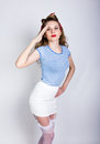 Portrait of a beautiful blond in a striped shirt, white skirt and lacy stockings, sailor saluting with a Yes Sir. Pin Up Royalty Free Stock Photo