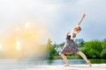 Portrait of beautiful blond young lady dancing like angel in light dress at water lake and sun lighting miracle flare Royalty Free Stock Photo
