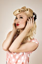Portrait of beautiful blonde girl listening to music retro pin up style Royalty Free Stock Photo