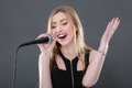 Portrait of a beautiful blonde young woman singing into micropho Royalty Free Stock Photo