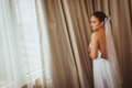 Portrait of beautiful bride brunette with closed eyes near window Stock Images