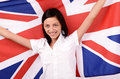 Portrait of a beautiful British girl smiling holding up the UK flag. Royalty Free Stock Images