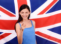 Portrait of a beautiful british girl smiling and pointing in front to you young woman standing with the uk flag the background Royalty Free Stock Photography