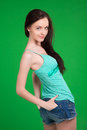 Portrait of beautiful brunette girl wearing shorts over green background Royalty Free Stock Photos