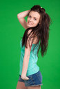 Portrait of beautiful brunette girl wearing shorts over green background Royalty Free Stock Photography