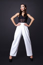 Portrait of beautiful brunette woman in a black blouse and white pants,. Fashion photo shot. Royalty Free Stock Photo