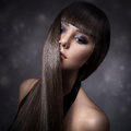 Portrait of a beautiful brunette woman with long straight hair on gray background Stock Photo