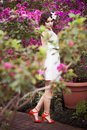 Portrait of a beautiful brunette woman in pink dress and colorful make up outdoors in azalea garden Royalty Free Stock Photo