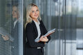 Portrait of beautiful businesswoman smiling and standing with folder in the office