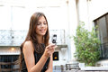 Portrait beautiful businesswoman using cell phone sitting classic coffee shop smiling outdoors Stock Photo