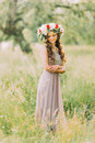 Portrait of beautiful charming young lady in flower wreath and white violet dress looking down Royalty Free Stock Photo
