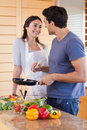 Portrait of a beautiful couple cooking with a pan Royalty Free Stock Images