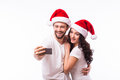 Portrait beautiful couple in santa hats in love taking romantic self portrait christmas young selfie photo together with mobile Royalty Free Stock Image