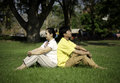 Portrait of beautiful couple sitting on ground in park relaxing Royalty Free Stock Photography