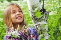 Portrait of a beautiful dreaming girl with a bouquet of flowers some white birch the park near the Royalty Free Stock Image