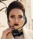 Portrait of beautiful elegant girl in beige coat and silk scarf fashion outdoor photo lady wearing luxurious on her head Royalty Free Stock Photo