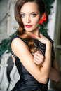 Portrait of beautiful elegant young woman in gorgeous evening dress over christmas background