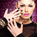 Portrait of a beautiful fashion woman with bright makeup black nails and pretty sexy face glamour girl posing at studio over Royalty Free Stock Photo