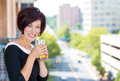 A portrait of a beautiful female businesswoman relaxing on a balcony on a sunny summer day drinking orange juice in new Stock Images