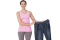 Portrait of a beautiful fit woman holding an old jeans Royalty Free Stock Photo