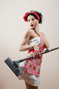 Portrait of beautiful funny sexy lady wearing apron & looking at camera surprised while vacuum cleaner sucked in her dress Royalty Free Stock Photo