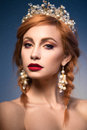 Portrait of a beautiful ginger woman with crown and red lips in the image of the bride.