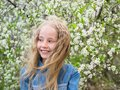 Portrait of a beautiful girl in a denim shirt next to a cherry tree. Portrait of laughing happy girl. Royalty Free Stock Photo