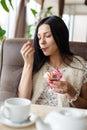 Portrait of beautiful girl having fun eating ice cream in coffee shop or restaurant, closeup Royalty Free Stock Photo