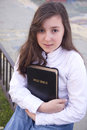 Portrait of beautiful girl holding bible