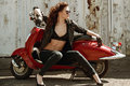 Portrait of a beautiful girl in leather jacket, brassiere and glasses near red  motorcycle Royalty Free Stock Photo