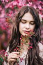Portrait of beautiful girl in a pink dress, looking down with half open lips, keeps on hand a twig with buds, close-up