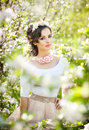 Portrait of beautiful girl posing outdoor with flowers of the cherry trees in blossom during a bright spring day Royalty Free Stock Photo