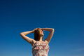 Portrait of the beautiful girl with raised hands looks aside against blue sky Stock Images