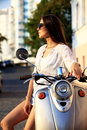 Portrait of a beautiful girl sitting on silver retro scooter, smiling and looking at the camera Royalty Free Stock Photo