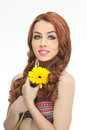 Portrait of beautiful girl in studio with yellow chrysanthemum in her hands. Sexy young woman with blue eyes with bright flower Royalty Free Stock Photo