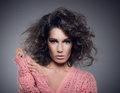 Portrait of beautiful glamour woman with curly hairs and pink sweater looking at camera Royalty Free Stock Photography