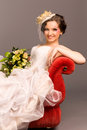Portrait of a beautiful happy bride on red sofa Royalty Free Stock Photos
