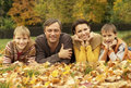 Portrait of a beautiful happy family lying in autumn park Stock Images