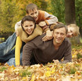 Portrait of a beautiful happy family lying in autumn park Royalty Free Stock Photography
