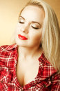 Portrait of a beautiful housewife girl next door with long blond hair in red casual shirt posing over wooden background close up Royalty Free Stock Photography