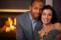 Portrait of beautiful interracial couple smiling young at home by fireplace Stock Images