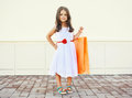 Portrait of beautiful little girl in dress with shopping bag Royalty Free Stock Photo