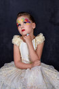Portrait of Beautiful little girl think in white dress red lips with painted face at dark background