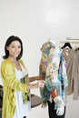 Portrait of a beautiful mid adult woman standing by mannequin in fashion shop Royalty Free Stock Photo